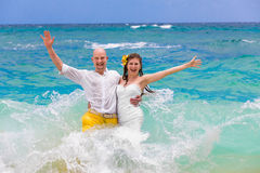Happy bride and groom having fun in the waves on a tropical beac Stock Photo