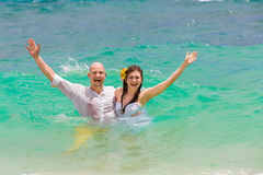Happy bride and groom having fun in the waves on a tropical beac Royalty Free Stock Images