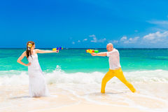 Happy bride and groom having fun in the waves on a tropical beac Royalty Free Stock Photography