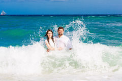 Happy bride and groom having fun in the waves on a tropical beach Stock Photo