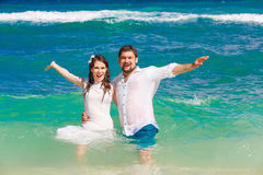 Happy bride and groom having fun in the waves on a tropical beach Royalty Free Stock Images