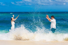 Happy bride and groom having fun in the waves on a tropical beach Stock Photos