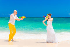 Happy bride and groom having fun in the waves on a tropical beach. Wedding and honeymoon on the tropical island.  Royalty Free Stock Photography