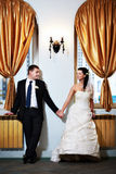Happy bride and groom hold each other's hand Stock Photos