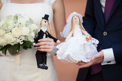 Happy bride and groom holding cute handmade dolls of husband and Royalty Free Stock Photography