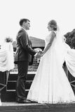 Happy bride and groom holding hands and looking at each other Stock Image