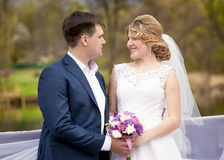 Happy bride and groom holding hands and looking at each other Stock Photography