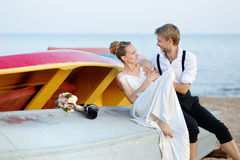 Happy bride and groom hugging by the sea Stock Images