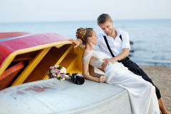 Happy bride and groom hugging by the sea Royalty Free Stock Photography