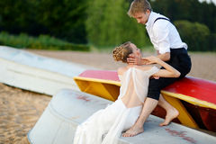 Happy bride and groom hugging by the sea Stock Photos