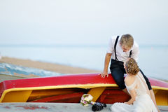 Happy bride and groom hugging by the sea Stock Photo