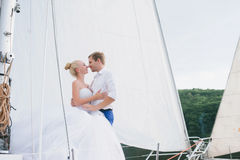 Happy bride and groom hugging on a yacht Royalty Free Stock Images