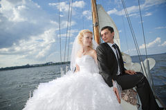 Happy bride and groom hugging on a yacht Stock Images