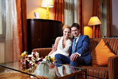 Happy bride and groom in interior of hotel room Stock Photo