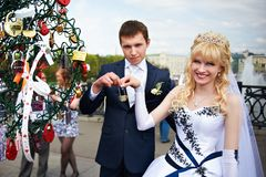 Happy bride and groom keep a love lock Royalty Free Stock Photography