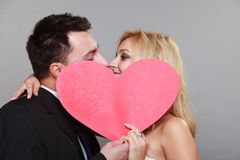 Happy bride and groom kissing behind red heart Stock Images