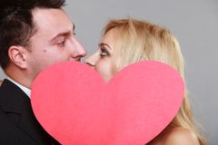Happy bride and groom kissing behind red heart Royalty Free Stock Photography