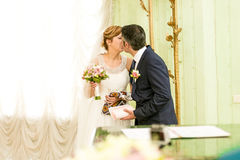 Happy bride and groom kissing first time at registry office Stock Images