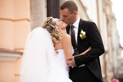 Happy bride and groom kissing on street against building Stock Photo