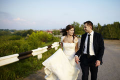 Happy bride and groom laughing smiling on the road on wedding da Royalty Free Stock Photos