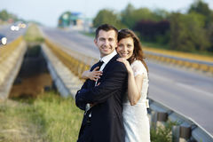 Happy bride and groom laughing smiling on the road on a wedding Royalty Free Stock Photography