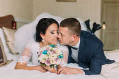 Happy bride and groom lay on bed in hotel room after wedding celebration. Newlyweds tenderly kissing Stock Image