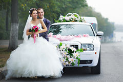 Happy bride and groom with lmo. Happy bride and groom near wedding limo stock image