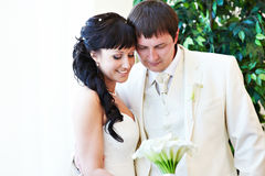 Happy bride and groom look at bouquet Stock Photo