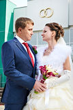 Happy bride and groom look at bouquet Stock Photos