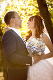 Happy bride and groom looking at each other at autumn park Stock Photos