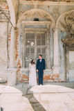 Happy bride and groom looking at each other standing in an old ruined brick window of ancient building Royalty Free Stock Photos
