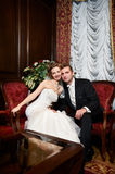 Happy bride and groom in luxury chairs Stock Photography