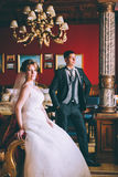 Happy bride and groom in luxury chairs in chic interiors Stock Image