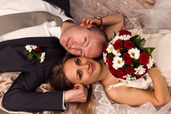Happy bride and groom lying Royalty Free Stock Images