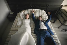 Happy bride and groom lying on bed at hotel room Royalty Free Stock Images