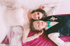 Happy bride and groom lying on bed Royalty Free Stock Images