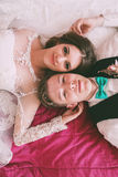 Happy bride and groom lying on crimson bed Royalty Free Stock Photo