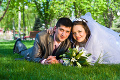 Happy bride and groom lying on grass Royalty Free Stock Image
