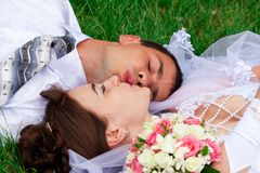 Happy bride and groom lying on a green grass Royalty Free Stock Images