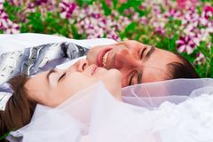Happy bride and groom lying on a green grass Royalty Free Stock Photography