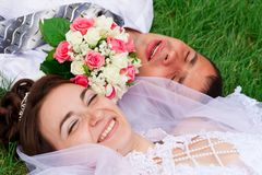Happy bride and groom lying on a green grass Stock Images