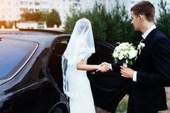 Happy bride and groom near car. Stock Photo