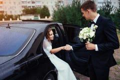 Happy bride and groom near car. Stock Photos