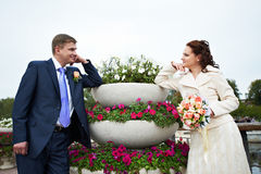 Happy bride and groom near flowerbed Royalty Free Stock Images