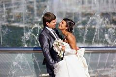 Happy bride and groom near fountain Stock Image