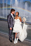 Happy bride and groom near fountain with rainbow Stock Photo