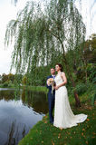 Happy bride and groom near lake Stock Photos