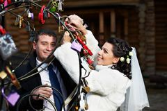 Happy bride and groom near metal tree Royalty Free Stock Photo