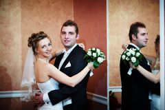 Happy bride and groom near mirror Royalty Free Stock Photography