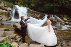 Happy bride with groom near a mountain waterfall. luxurious wedding dress. Success life. Marriage couple outdoor royalty free stock photography